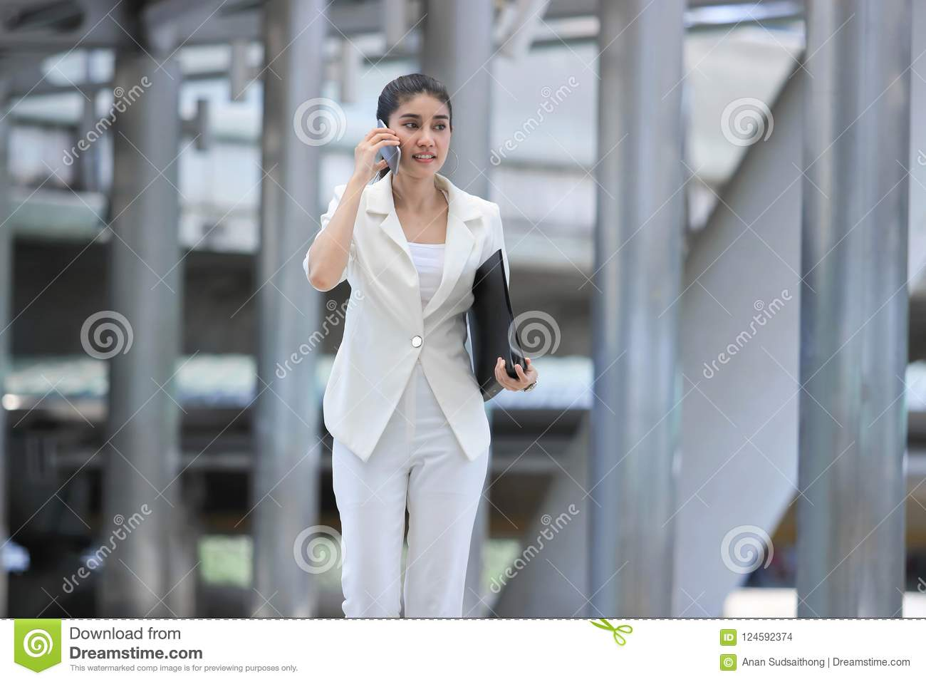attractive-young-asian-business-woman-talk-phone-walking-to-office-124592374