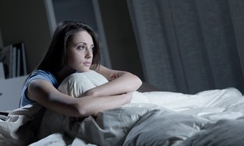 woman-staring-out-from-bed-350