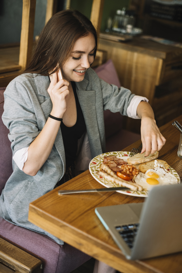 young-woman-eating-food-restaurant-talking-mobile-phone_23-2147871280