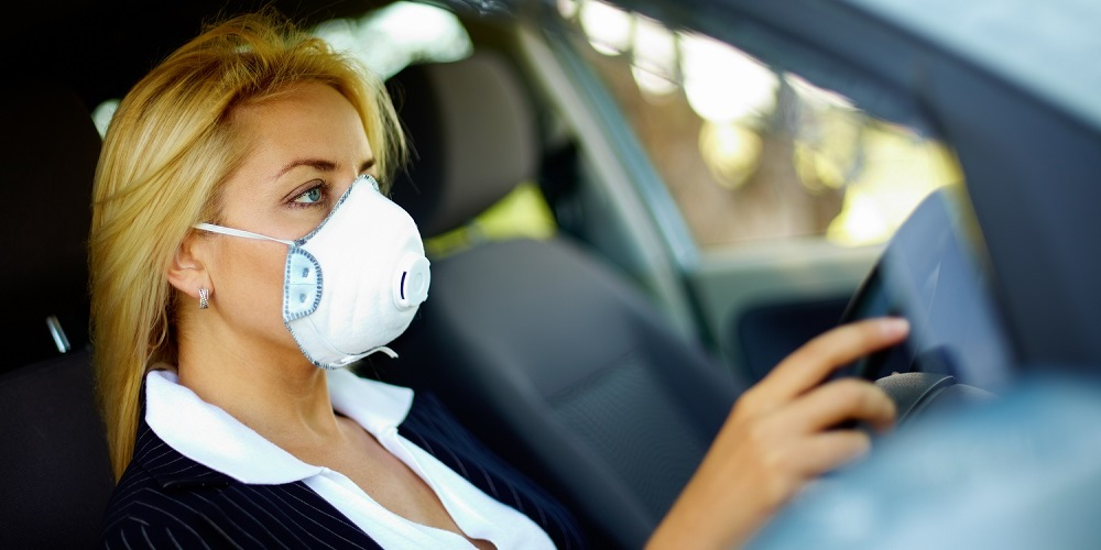 Photo of blond female wearing respirator while driving car in polluted area